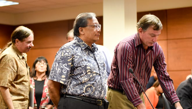 In this Aug. 23 file photo, David Sablan, center, former board chairman of the Guam Housing and Urban Renewal Authority, stands next to his attorney Sam Teker, right, at his arraignment at the Superior Court of Guam.