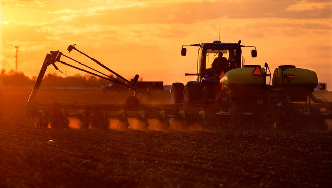 A central Illinois corn and soybean farmer races against a setting sun to plant seed corn in 2014.