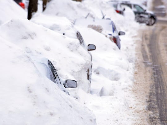 A line of cars sit buried in snow banks in Somerville, Mass., Tuesday, Feb. 10, 2015.
