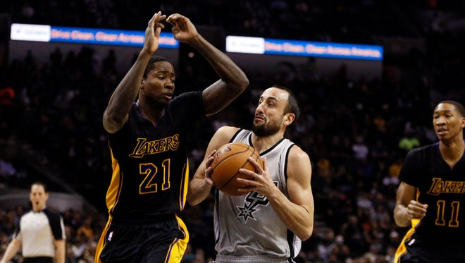 San Antonio Spurs shooting guard Manu Ginobili (20, R) drives to the basket as Los Angeles Lakers power forward Ed Davis (21) defends during the first half at AT&T Center.