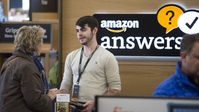An employee helps a customer at the new Amazon Books store at University Village in Seattle, Washington on November 3, 2015.  Twenty years after pioneering the virtual bookstore, Amazon went brick-and-mortar.   T