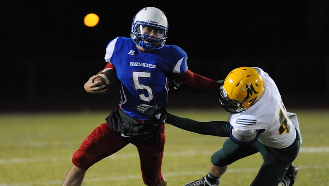Reno's Jeremy Smith escapes the clutches of a Bishop Manogue defender during last week's playoff game.