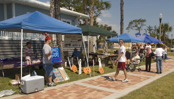 Visitors check out the booths during the Coastal Encounters Festival at Navarre Park.