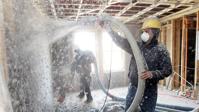 John Bowman of RJ Insulation sprays insulation between the wall studs of one of the 48 units of the Northern Kentucky Scholar House under construction in Newport.