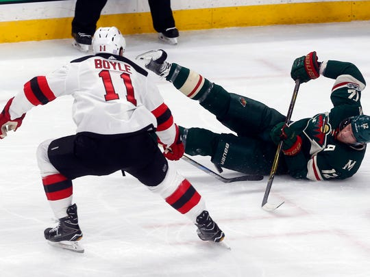 Minnesota Wild's Eric Staal, right, falls as he and New Jersey Devils' Brian Boyle battle for the puck in the first period of an NHL hockey game Monday, Nov. 20, 2017, in St. Paul, Minn. (AP Photo/Jim Mone)