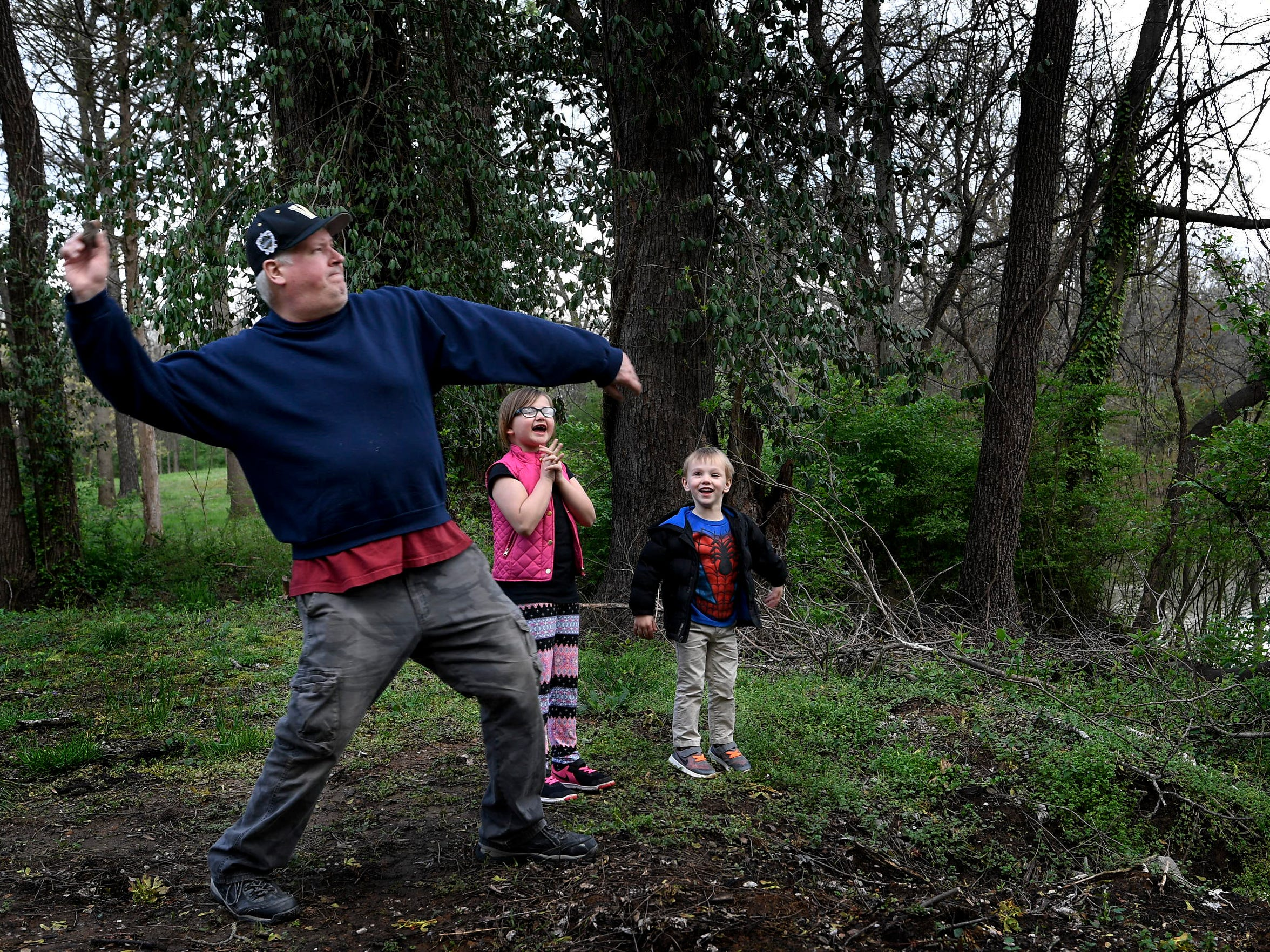 Mickey Baltz throws stones into the Cumberland River as grandchildren Braelyn and Tyler Hardin cheer as they visit Mickey's childhood home in Nashville on March 30, 2018.