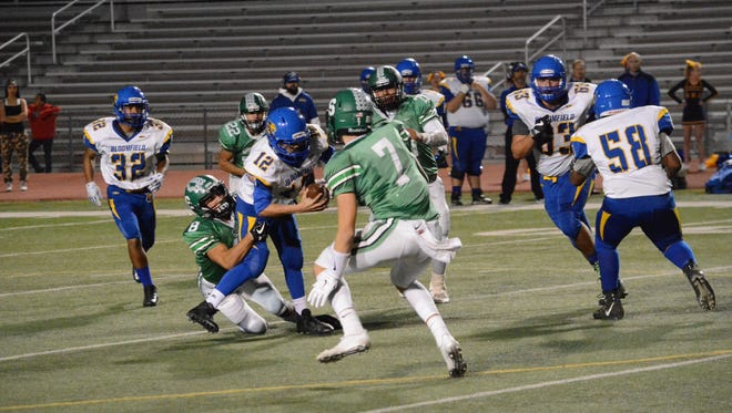 Farmington's Mason Ross, No. 8 in green, brings down Bloomfield quarterback Vince Marquez for a sack during the second quarter of Thursday's District 1-5A game at Hutchison Stadium.