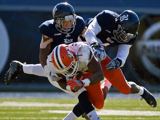 UTEP quarterback Mark Torrez, center, is tackled by Rice cornerback J.T. Blasingame, left, and linebacker Alex Lyons, right, during the second half of an NCAA college football game, Saturday, Nov. 19, 2016, in Houston. Rice won 44-24.