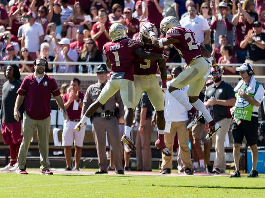 Florida State's defense celebrates an interception during the first quarter of the Seminoles 27-24 victory over Syracuse at Doak Campbell Stadium in Tallahassee, FL.