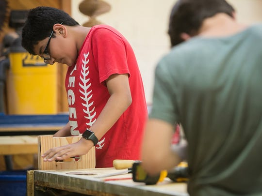 Darsh Patel, 13, works in the carpentry class as New