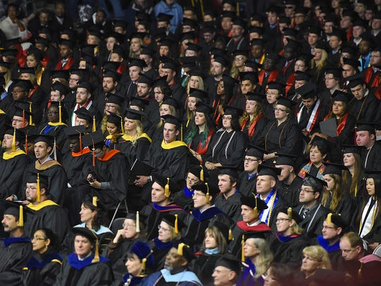Graduates wait to receive their degrees during fall