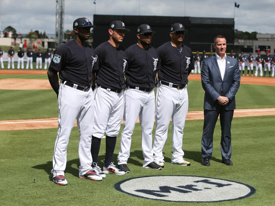 The Detroit Tigers Justin Upton, Ian Kinsler, Francisco Rodriguez , Victor Martinez and Chris Ilitch stand by the MR I logo in honor of  Mike Ilitch before action against Baltimore on Friday, February 24, 2017 at Publix Field at Joker Marchant Stadium in Lakeland, Florida.