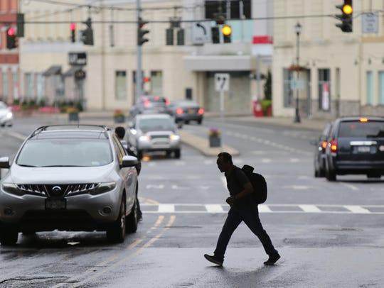 A pedestrian crosses Westchester Avenue in Port Chester