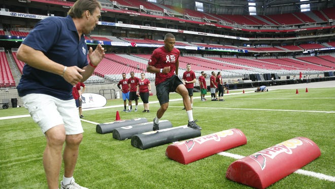 Staff Sgt. Justin Nesbitt runs a drill during the USAA's NFL Boot Camp event at University of Phoenix Stadium in Glendale, Ariz. August 14, 2017. About 70 service members from Luke Air Force Base performed drills similar to those used by NFL coaches to evaluate NFL talent.