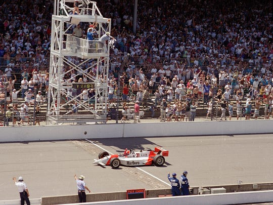 Al Unser Jr. waves a fist as he crosses the finish line and receives the checkered flag to win the 1994 Indianapolis on May 29, 1994 at the Indianapolis Motor Speedway. The last three laps of the race were run under yellow after Stan Fox's car crashed. It was Unser's second 500 win.
