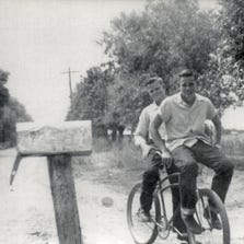 Bob and Gene Taylor ride a bicycle on Lehi Road, then a dirt road, in 1942. The dirt road was lined by large Cottonwood trees and agricultural fields.