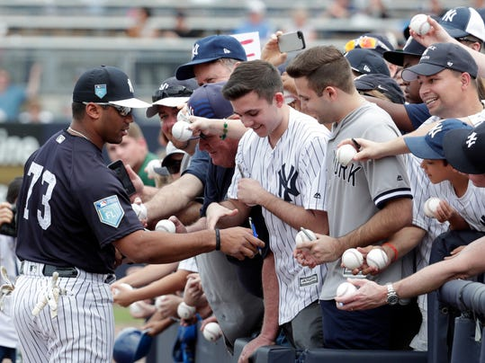 Seattle Seahawks quarterback Russell Wilson, signs autographs while working out with the New York Yankees before a baseball spring exhibition game against the Atlanta Braves, Friday, March 2, 2018, in Tampa, Fla. (AP Photo/Lynne Sladky)