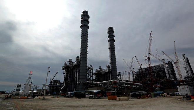 In this Oct. 21, 2013 photo, the H2S and CO2 absorber vessels are shown in silhouette at the Mississippi Power's Kemper County energy facility in central Mississippi near DeKalb. Construction continues at the power plant that is designed to use a soft form of coal called lignite in a gasification process to generate power. The plant, America?s newest, most expensive coal-fired power plant is hailed as one of the cleanest on the planet, thanks to government-backed technology that removes carbon dioxide and keeps it out of the atmosphere. Once the carbon is stripped away, it will be used to do something that is not so green at all ? extract oil. Power companies sell the carbon dioxide to oil companies, which pump it into old oil fields to force more crude to the surface. (AP Photo/Rogelio V. Solis)