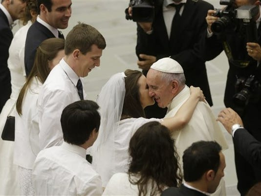 Pope Francis greets newlyweds during the general audience in the Paul VI hall at the Vatican, Wednesday, Aug. 5, 2015. Pope Francis says divorced Catholics who remarry and their children deserve better treatment from the Catholic church.