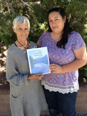Event organizers Mary Burton Riseley and Emily Aversa hold a flyer for the La Capilla sunrise gathering in honor of the Pope's historic visit.