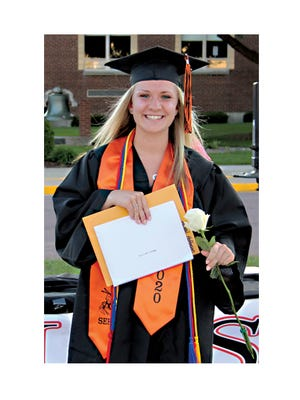 Abby Hoffmann stopped for a photo after receiving her diploma and packet of awards and scholarships. Abby is wearing the Gold Cord for academic achievement, Blue Cord for Minnesota Honor Society membership, and Red Cord from the Red Cross for participation in blood drives.