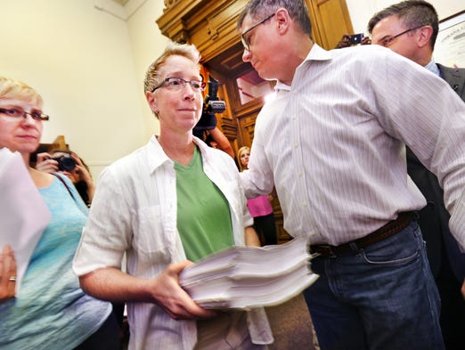 Melody Layne, left, and Tara Betterman, who were married in New York, help to deliver some of the more than 12,000 signatures gathered by Hoosiers Unite For Marriage in opposition to the state appealing Wednesday's ruling tossing out the state's ban on same-sex marriage, to the office of Indiana Attorney General Greg Zoeller at the Statehouse in Indianapolis on Friday, June 27, 2014.