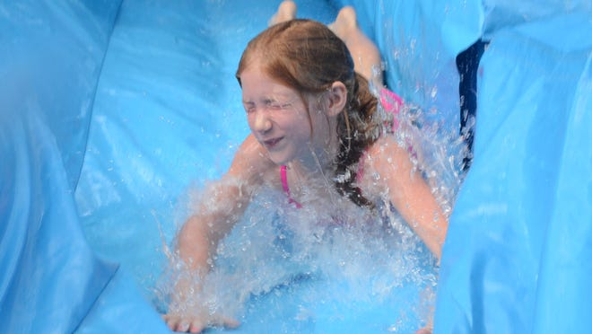 McKenzy Guillot plays on a water slide Saturday at Water Play Day at the Alexandria Zoo. Children played on water slides, in sprinklers and learned about oceans and rivers.
