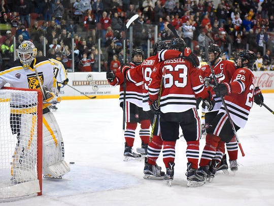 St. Cloud State players celebrate a goal by Mikey Eyssimont