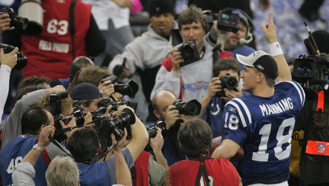 Colts QB Peyton Manning faces a crowd of photographers as he waves to people in the stands after the game Sunday at the RCA Dome Sunday Jan. 21, 2007. The win earned the Colts a trip to the Super Bowl.