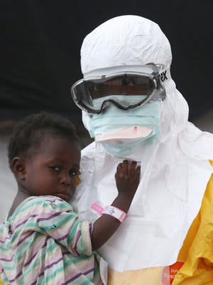 A Doctors Without Borders health worker in protective clothing holds a child suspected of having Ebola on Oct. 5, 2014, in Paynesville, Liberia.