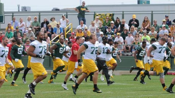 Green Bay Packers players run during warmups at Thursday's minicamp practice at Ray Nitschke Field.