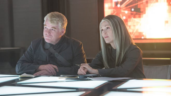 "This image released by Lionsgate shows Philip Seymour Hoffman, left, and Julianne Moore in a scene from ""The Hunger Games: Mockingjay - Part 1,"" set for release on Nov. 21."