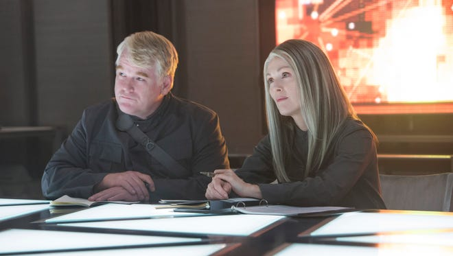 "This photo released by Lionsgate shows, Philip Seymour Hoffman, left, as Plutarch Heavensbee and Julianne Moore as President Coin in a scene from the film, ""The Hunger Games: Mockingjay - Part 1."" The movie releases on Nov. 21, 2014. (AP Photo/Lionsgate, Murray Close) ORG XMIT: CAET428"