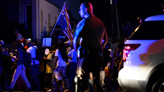 Police officers stand along a street as demonstrators protest the shooting death of Michael Brown in Ferguson, Mo., Monday.