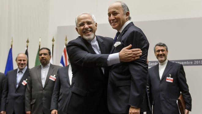 Iranian Foreign Minister Mohammad Javad Zarif and French Foreign Minister Laurent Fabius react after a landmark deal on Iran's nuclear program was reached in Geneva.