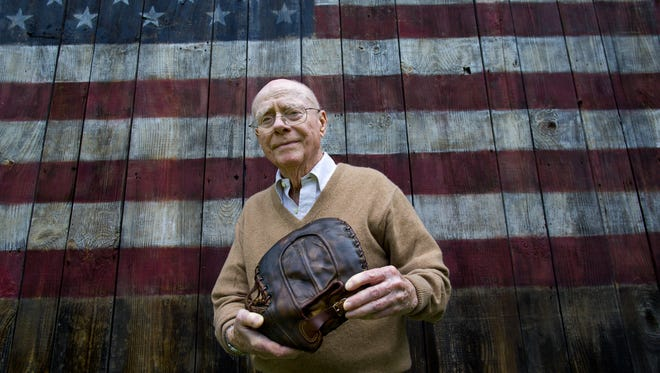 In this June 30, 2014, file photo, Howard Henderson, who as a boy in New York played catch with baseball legend Lou Gehrig, poses for a photo near his Greenwich, Conn., home, holding a signed baseball mitt given to him by Gehrig when he was young boy. The autographed baseball glove sold at auction for $287,500 on Tuesday, July 15, 2014, officials with Hunt Auctions said.