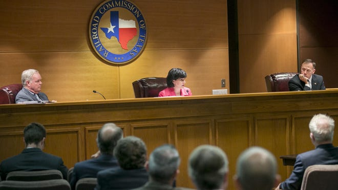 Texas Railroad commissioners Wayne Christian, from left, Chairwoman Christi Craddick and Ryan Sitton sit at a commission meeting in 2018. The agency is being sued over an alleged open meetings violation that involved the easing of environmental rules.