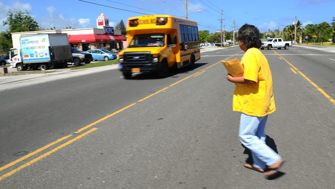 """Mongmong resident """"Kika"""" Jesus waits for passing traffic as she makes her way across Route 10 in Mangilao on Monday, April 11. Jesus, who used the Guam Mass Transit Authority Redline bus to be transported to the area, expressed concern for her safety, as well as other passengers heading to the Department of Public Health, when they have to cross the busy roadway, after being dropped on the opposite side of the street near the Pay-Less Supermarket parking lot."""
