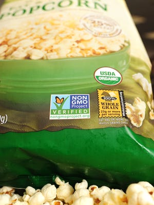 A label on a bag of popcorn indicates it is a non-GMO food product.