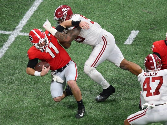Georgia Bulldogs quarterback Jake Fromm (11) is sacked by Alabama Crimson Tide defensive lineman Raekwon Davis (99) during the fourth quarter in the 2018 CFP national championship college football game at Mercedes-Benz Stadium