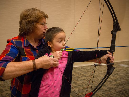 Volunteer Shirley Madsen helps 4-year-old Nevaeh Duran fire an arrow during the Mesilla Valley Outdoor Expo at the Las Cruces Convention Center on Saturday.