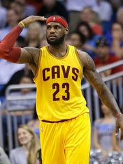 Cleveland Cavaliers' LeBron James makes gestures to teammates during the final moments of an NBA basketball game against the Orlando Magic, Friday, Dec. 26, 2014, in Orlando, Fla. Cleveland won 98-89. (AP Photo/John Raoux)