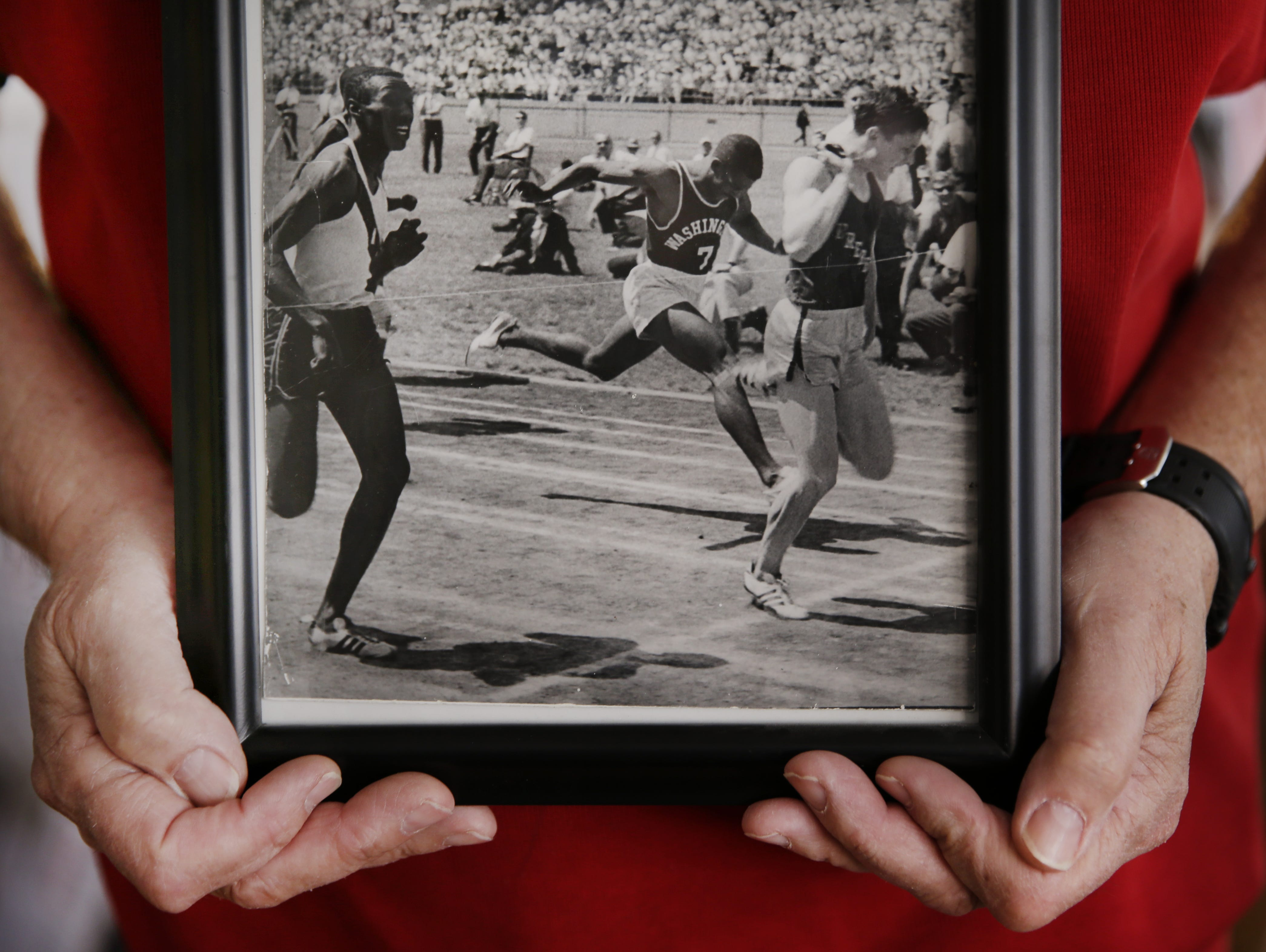 Clyde Peach holds a photo of himself breaking the tape in the 100 in May 1966.