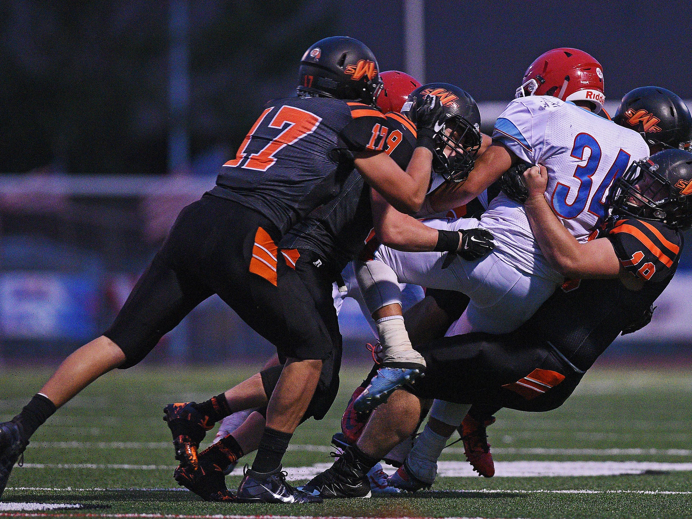 Lincoln's Cory Fichter (34) is brought down by a group of Washington defenders in 2016. The number of players in high school football has gradually decreased since 2011.