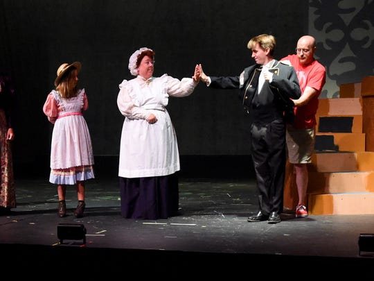 Actors Diane Kester as Mrs. Brill and Austin Boyette as Robertson Ay give each other a high-five on stage. Kate Cummings as Jane Banks stands to the left with costume assistant Jon Bayne determining alterations needing to be made to Boyette's outfit on the right.