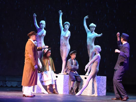 Lighting illuminates the ensemble actors portraying statues as well as other cast members on stage during rehearsal on August 3, 2015.