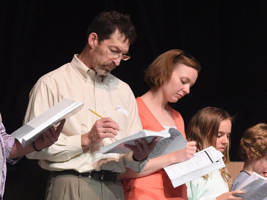"""Actors Tom Pereles as """"George Banks,"""" Melissa Dull as """"Winifred Banks"""" and Kate Cummings as Jane Banks review lines while on stage during a rehearsal on July 6, 2015."""