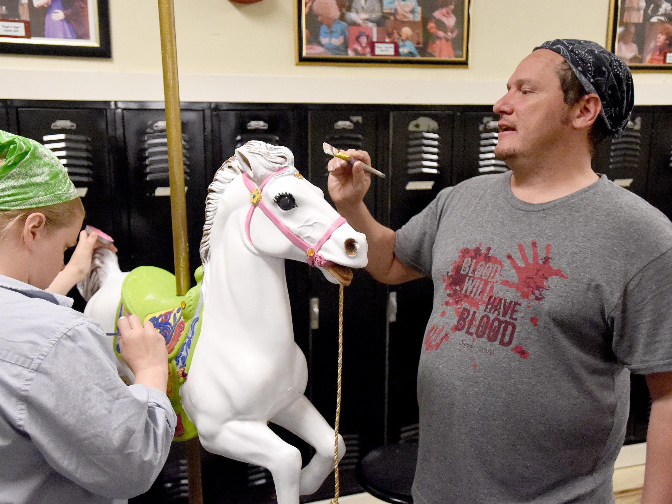 Director Hank Fitzgerald picks up a brush during a work session and decides to add eye lashes to the carousel horse that will be used by the character Mary Poppins in their production.