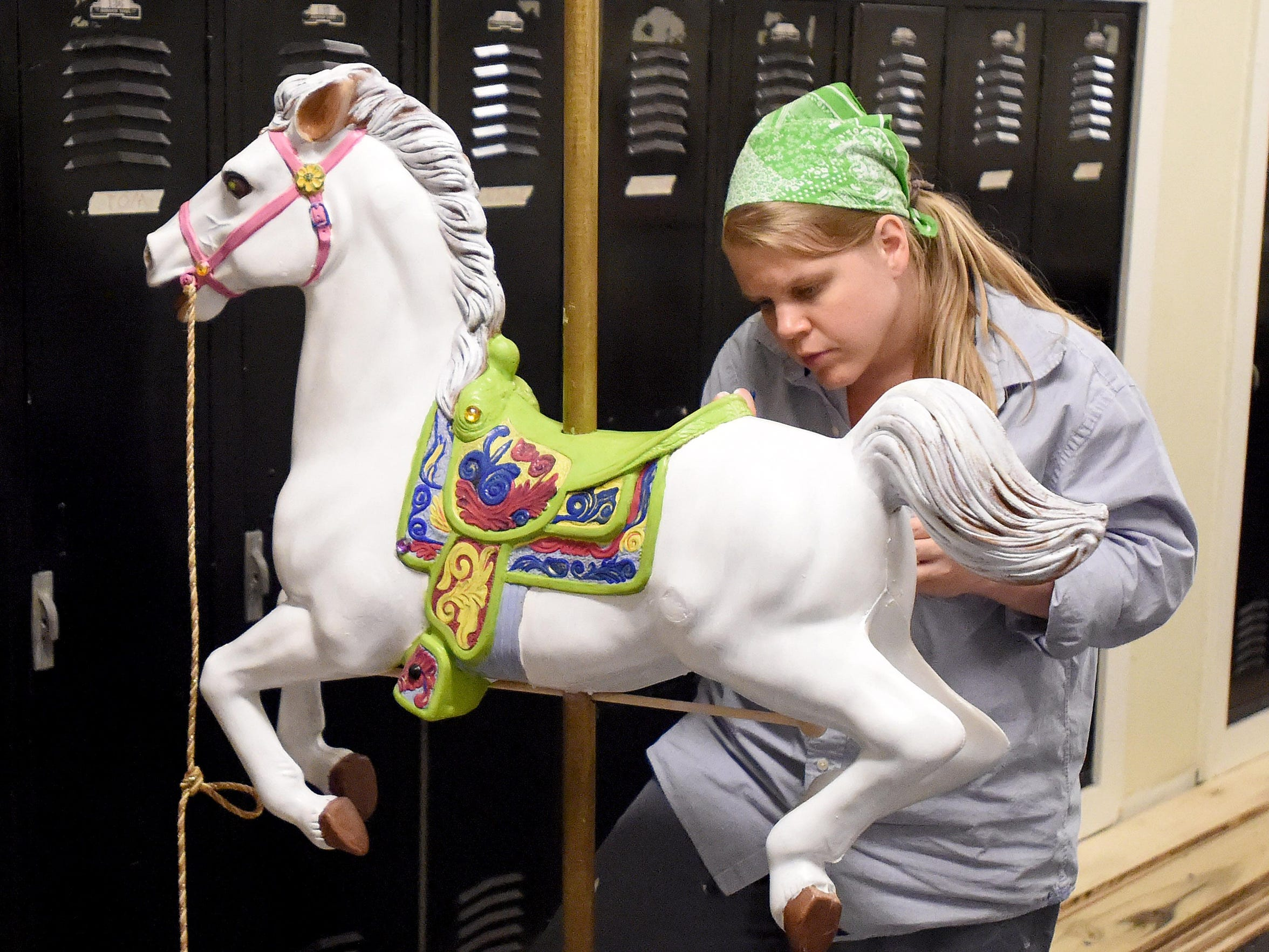 Kristin Gaffney paints the carousel horse during an