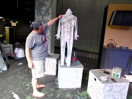 During a work session, director Hank Fitzgerald holds up one of the statue character body suits up over where the actor will stand to see how well the suit matches the painted pattern of the base.